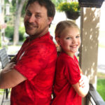 Man and young girl back to back wearing red shirts standing on deck smiling happy healthy wellness