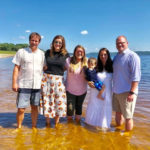 Family with baby standing in water lake health wellness chiropractic smiling
